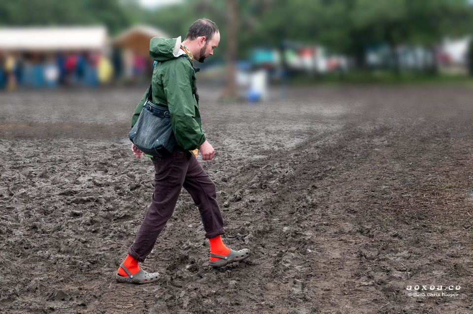 Man walks in mud at utopifest aoxoa
